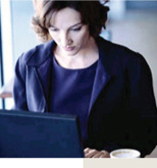 Image of a Businesswoman in blue suit working on her computer in a non-office environment