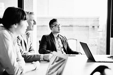 一群商务人士坐在玻璃墙办公室的一张桌子旁,所有人都看向房间的另一头。