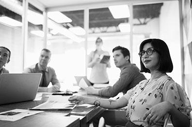 坐在会议桌旁的办公室工作人员团队——所有人都朝着同一方向看,大概是在看屏幕上的演示文稿。