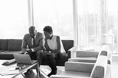 职业女性和男性坐在高层建筑办公室的咖啡桌旁,看着一台笔记本电脑。