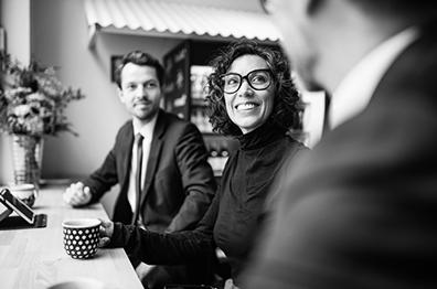 一個專業小組的三名員工一同微笑著喝咖啡。標題=