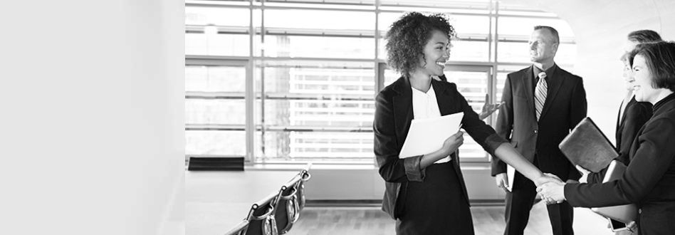 一群專業人士上班族站在會議桌旁,兩位女士握手並互相微笑。